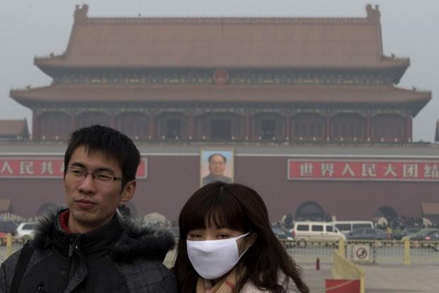 Chinesa utiliza máscara para se proteger do ar poluído registrado em Pequim (Foto: Ng Han Guan/AP)