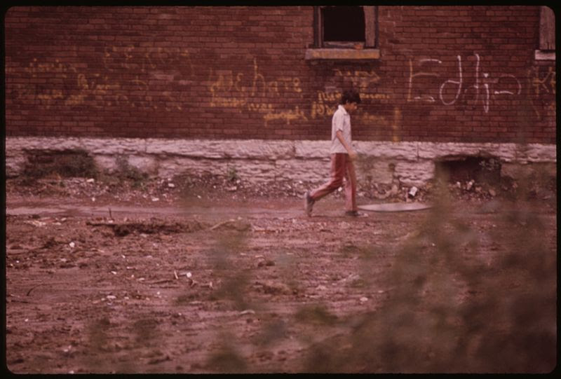 File:MULKY SQUARE BOY WALKS PAST BUILDING MARKED FOR DEMOLITION TO MAKE WAY FOR A NEW INTERSTATE HIGHWAY (I-635). THE... - NARA - 553506.jpg