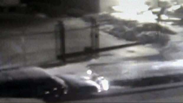 This security camera footage shows the tow truck's flatbed, right, striking the front of J.D. McIntosh's GMC Suburban, left.