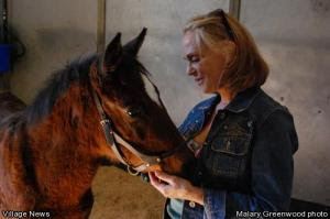 """Malary Greenwood photo - """"Foster Mom"""" Linda Harris talks sweetly to her rescued foal, Morning Star."""