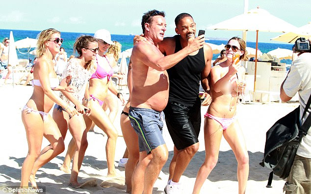 Wait there: Will Smith looked to be very much in demand as he walked around the beach in Ibiza on Thursday