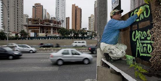 Carlos Adão escreve o próprio nome em casa abandonada na avenida Nove de Julho, em SP; economista criou o hábito há 16 anos