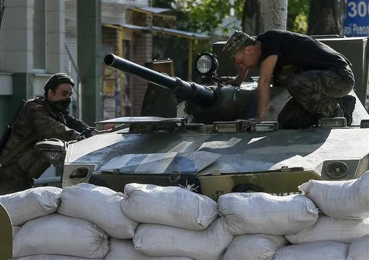 An armored personnel carrier is seen near a barricade around the state security service building in Slaviansk, April 26, 2014. REUTERS-Gleb Garanich