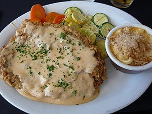 A white oval plate with chicken fried steak co...