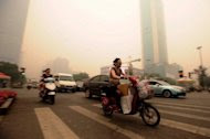 Chinese motorists wear masks as they make their way along a busy intersection in Wuhan on June 11. Wuhan was blanketed by thick yellowish cloud Monday, raising fears of pollution among its nine million inhabitants, residents told AFP. Witnesses said the haze appeared suddenly in the morning, and residents rushed to put on face masks. (AFP Photo/Str)