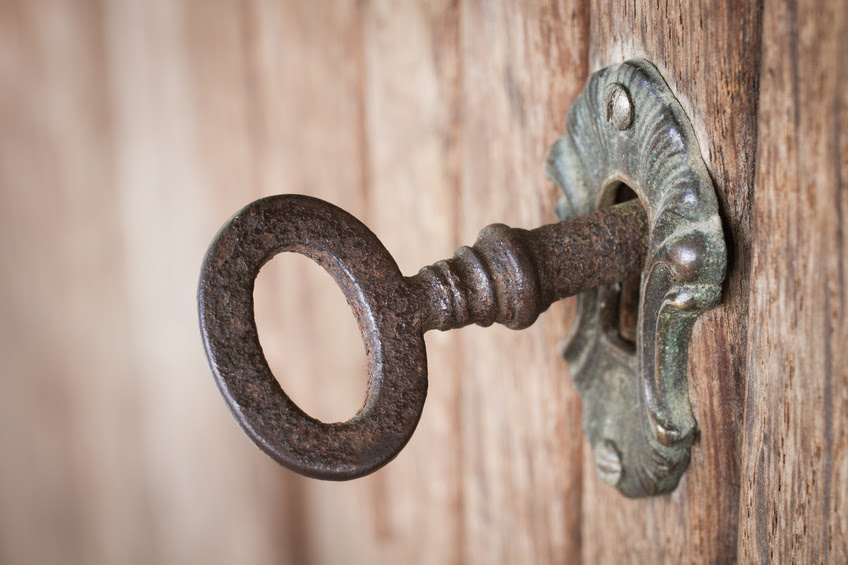 Close-up shot of an old rusty key inside a keyhole