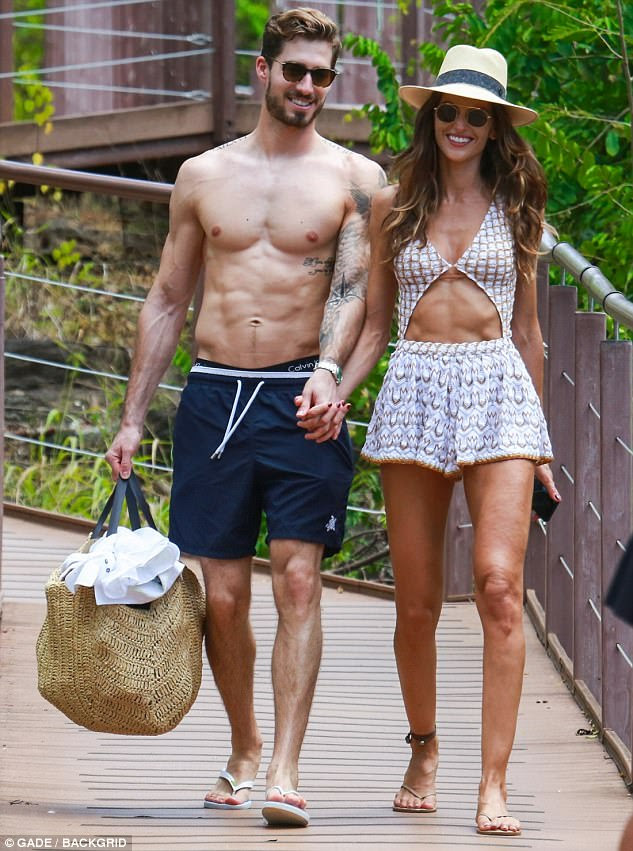Ab-tastic couple: The model later slipped on a white printed playsuit with cutaway detailing as she enjoyed a stroll with soccer star beau Kevin Trapp, 27