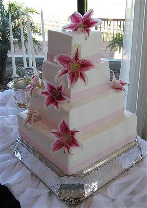 Four tier white rectangular wedding cake with fresh