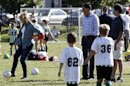 U.S. Republican presidential nominee and former Massachusetts Governor Mitt Romney and his son Tagg watch Ann Romney kick a soccer ball as they watch a children's soccer game in Belmont, Massachusetts