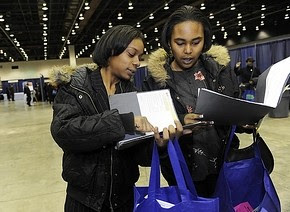 Kesha Calhoun, 25, left, and Kristin Merritt, 20, both of Detroit, share notes at a Cobo job fair. Michigan leads the nation in unemployment. (Clarence Tabb Jr. / The Detroit News) by Pan-African News Wire File Photos