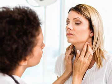 Una doctora le hace un examen físico de tiroides a una mujer joven