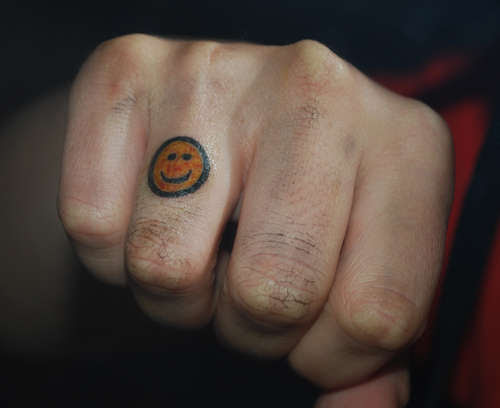 Smiley Face On Finger Tattoo