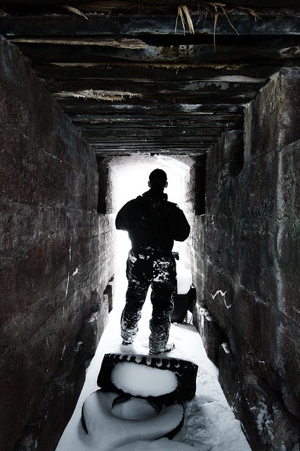 A person silhouetted in a ruined tunnel.