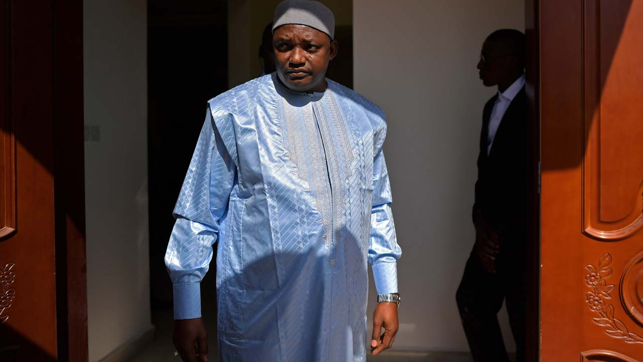 "The Gambia's President Adama Barrow arrives to speaks at his first press conference in The Gambia, as the country's newly elected leader, on January 28, 2017 in Banjul. West African nations plan to scale back a military force that secured the return to The Gambia of new President Adama Barrow to take power, the force commander said January 27. The mission of the Economic Community of West African States (ECOWAS) regional bloc will see ""a progressive reduction"" in numbers, Senegalese General Francois Ndiaye said in a statement a day after the newly elected leader flew back to his homeland. CARL DE SOUZA / AFP"