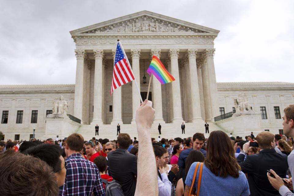 FILE - In this Friday June 26, 2015 file photo, a man holds a U.S. and a rainbow flag outside of the Supreme Court in Washington after the court...