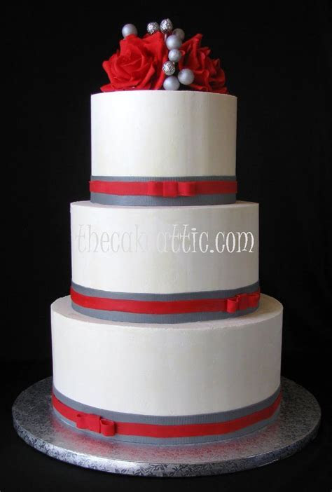 Buttercream wedding cake with red sugar roses and ribbons