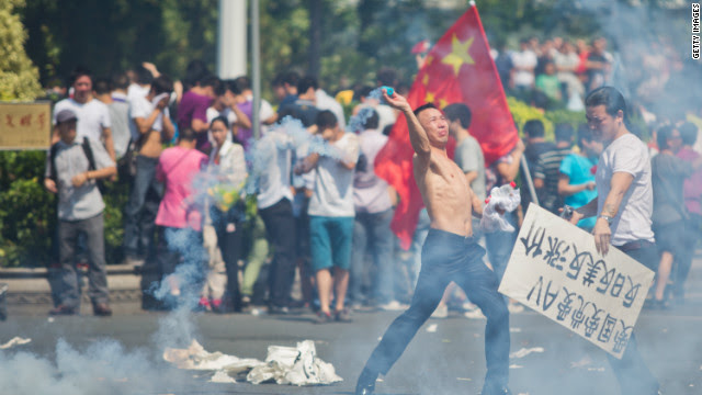 A protester hurls a gas cannister during a demonstration over the disputed Diaoyu Islands, which is also known as Senkaku by Japan, in Shenzhen, China.