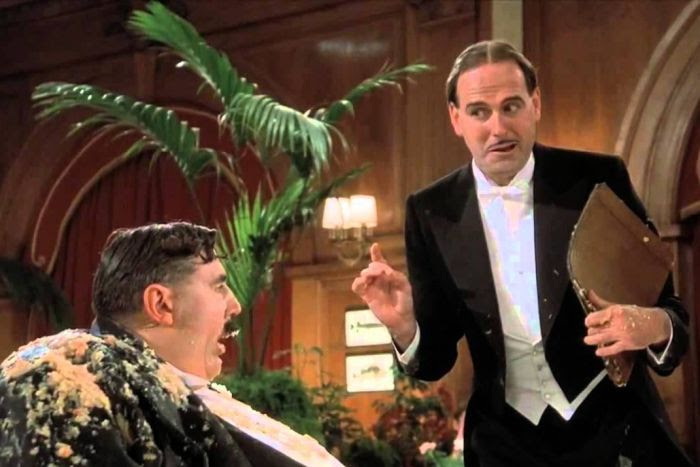 The maître d' (played by John Cleese) tempts Mr Creosote into ordering more food.