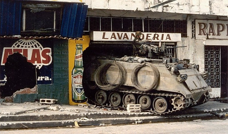 An armored vehicle stands guard in the rubble of a laundromat, near other destroyed civilian shops.