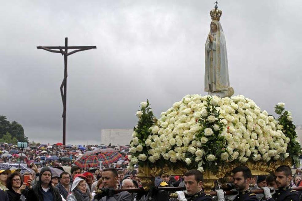 Imagem de Nossa Senhora de Fátima é carregada por fiéis durante cerimônia do dia 20 de abril, em Fátima, na região central de Portugal  (Foto: José Manuel Ribeiro / AFP)