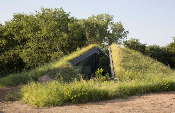 "This house, which sits comfortably under a patch of grass in Texas, was designed based on the vernacular of the ""pit house"", which is one of the oldest housing types in North America and is typically sunken."