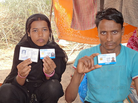 "Yasmin Ara, 21, and her husband, Mohammad Zakaria, 22, pose with their UNHCR issued asylum seeker cards and the Myanmar government issued white colored ""state guest"" card, at a makeshift camp in New Delhi on May 11, 2012."