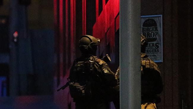 Armed tactical response police personnel stand watch into the evening near a cafe under s