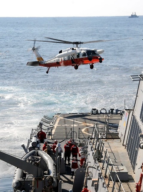 Japan coast guard helicopter prepares to land aboard USS Fitzgerald.