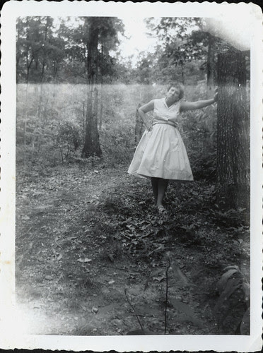 Girl in white dress leaning on tree