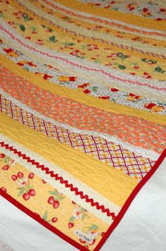 quilt...so cheerful!  How simple and effective - great baby quilt idea with rickrack and maybe even some lace for a little girl