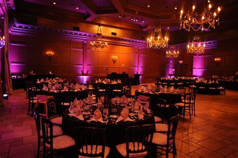 Red & orange ballroom with pink uplighting and dark linens