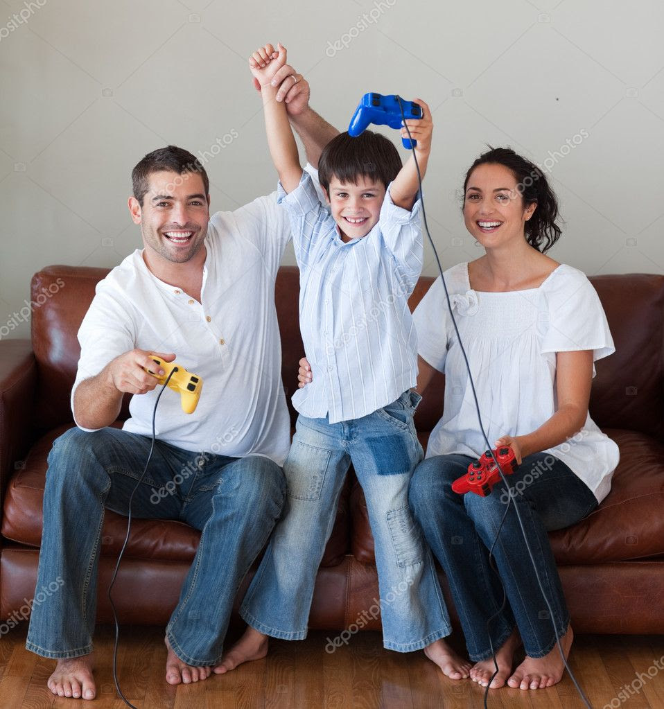 Happy family playing video games in the living-room | Stock Photo ...