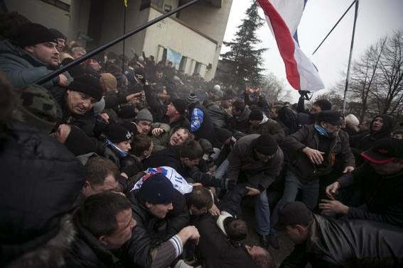 Ukrainian men help pull one another out of a stampede as a flag of Crimea is seen during clashes at rallies held by ethnic Russians and Crimean Tatars near the Crimean parliament building in Simferopol in this February 26, 2014 file photo.      REUTERS-Baz Ratner-Files