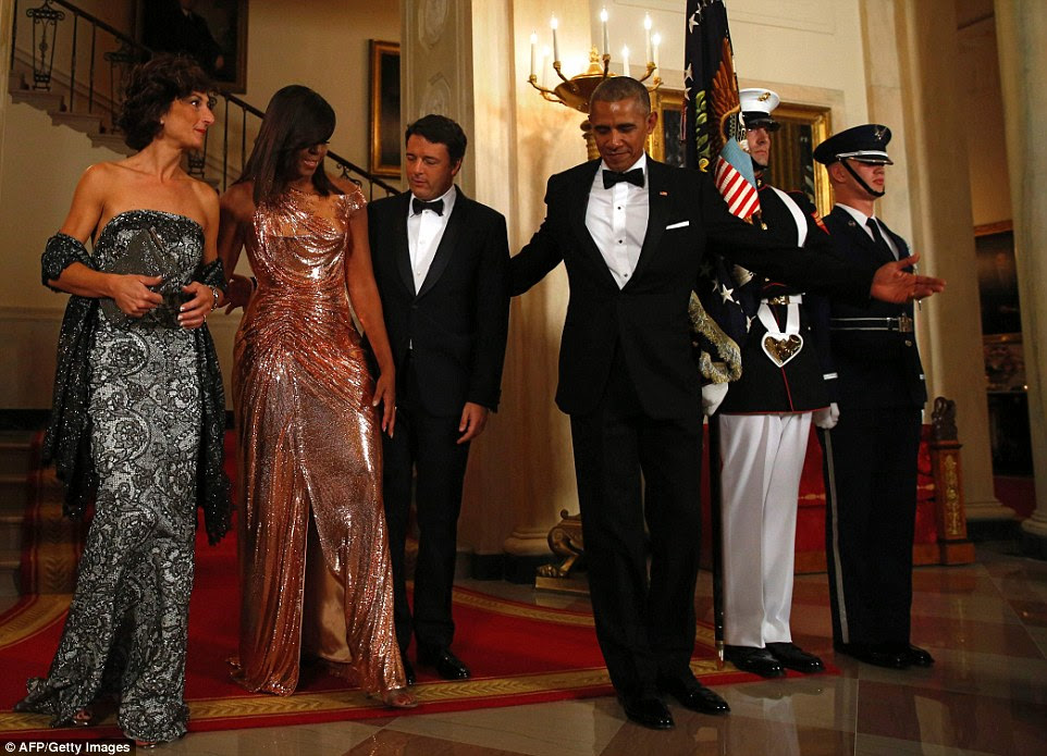 Easy does it: Italy's PM helps Michelle navigate off the carpet and onto the marble floor with a guiding hand on the back