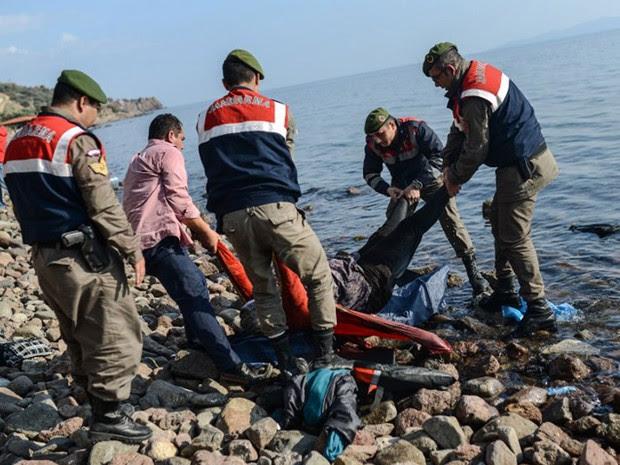 Guardas turcos retiram corpo de migrante na costa do Mar Egeu. Pelo menos 33 migrantes morreram em naufrágio neste sábado (30) (Foto: Ozan Kose / AFP)