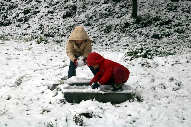 Dos niños juegan con la nieve en la carretera de les Aigües de Barcelona