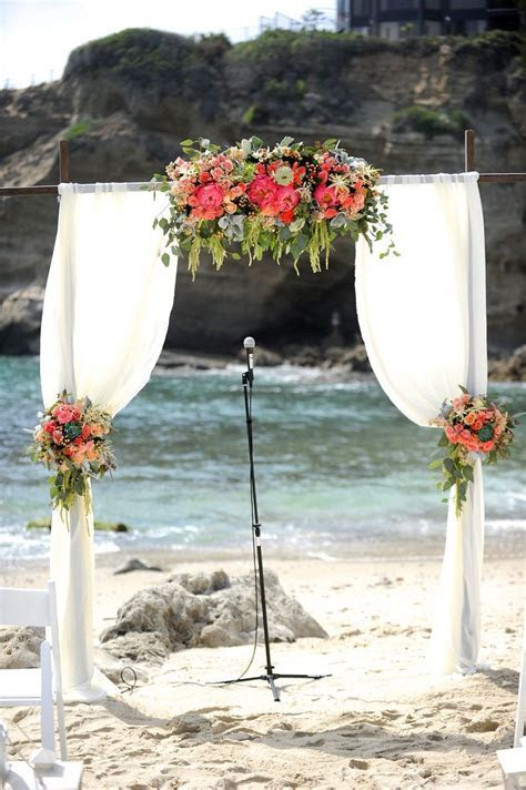 Wood wedding arch with draping fabric and flowers. Coral