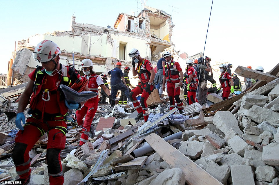 The 6.2-magnitude quake struck at 3.30am local time this morning while villagers slept in their beds. Rescuers are pictured walking through the rubble in Amatrice