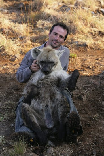 Кевин Ричардсон обнимает гиену. Фото