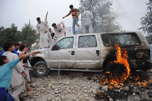 """Afghanistan youth destroy United States embassy vehicles after civilians were killed by the SUVs. Demonstrators chanted """"Death to America"""" and prompted the dispatch of military occupation forces to put down the unrest. by Pan-African News Wire File Photos"""
