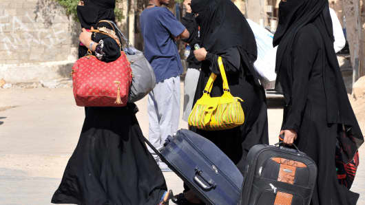 Foreign workers carry their belongings as they leave the Manfuhah neighbourhood of the Saudi capital Riyadh