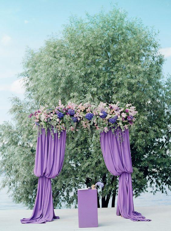 eine lila Hochzeit Bogen mit Vorhängen, üppigen Blüten und viel grün wirkt sehr auffällige
