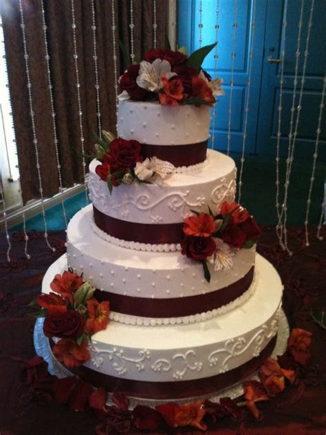 wedding cakes with snowflakes and burgandy ribbon