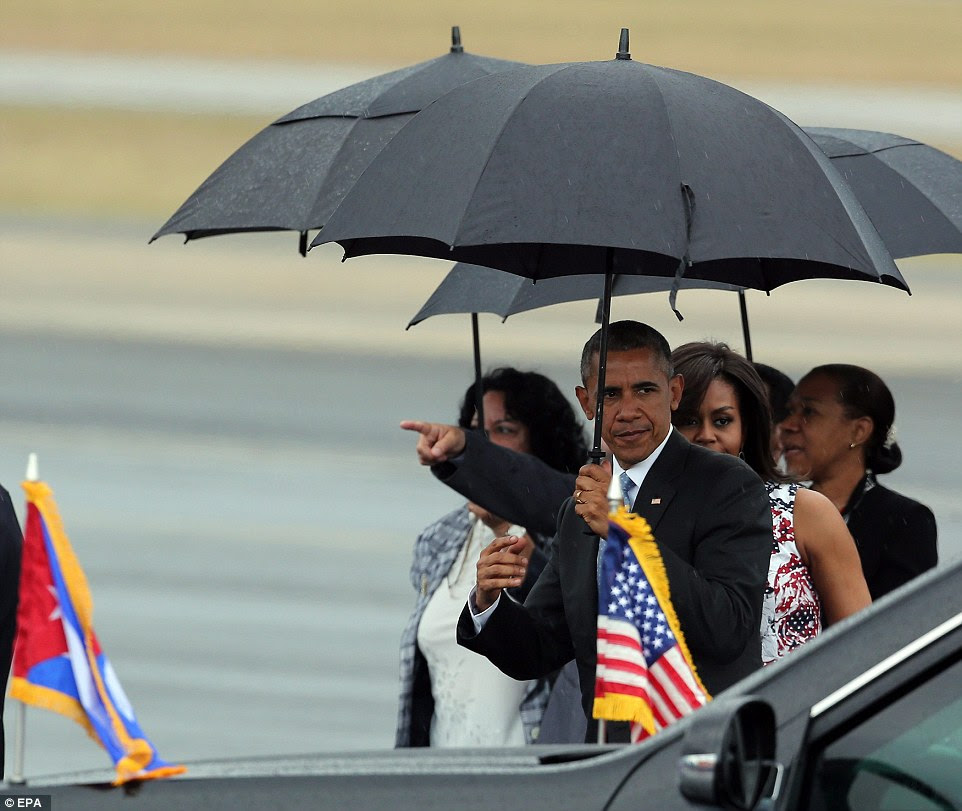 Obama points to the crowd as he heads to his limousine in the rain. He prepared to meet with U.S. embassy staff and go on a tour of Old Havana after getting off the plane