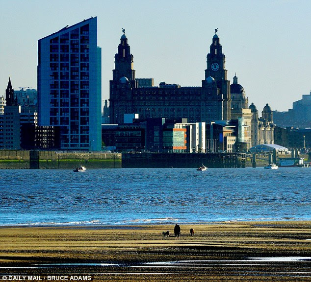 Crisp: Walkers enjoy the view of Liverpool city centre across the Mersey from the shore of New Brighton