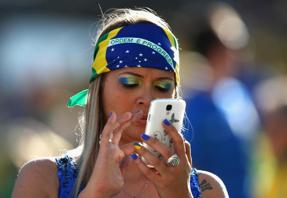 A Brazilian fan stayed connected to her mobile phone before the opening ceremony of the 2014 FIFA World Cup Brazil before the Group A match between Brazil and Croatia at Arena de Sao Paulo on June 12.