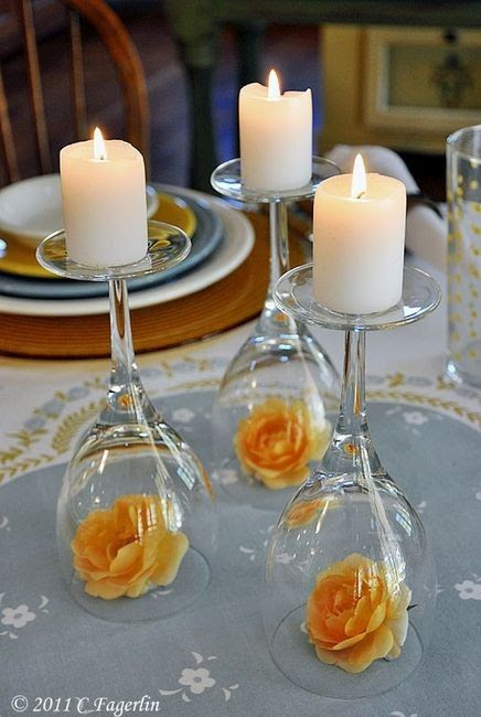 This is SO cute. Turning wine glasses upside down and putting flowers underneath for candle holders.