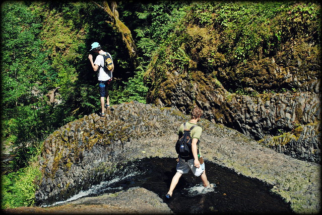 Hikers getting up close and personal with the edge of Triple Falls