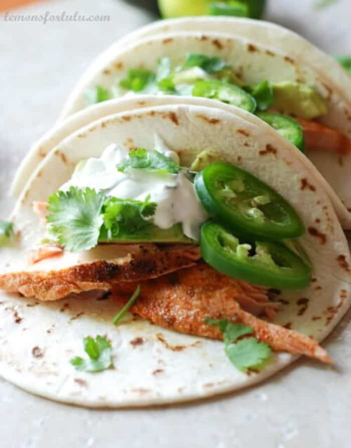 Simple salmon fish tacos with fresh jalapeños and a creamy topping!