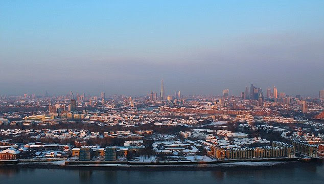 Peering across the river and into the city, the footage shows London during the daytime before emerging overnight covered in a fresh blanket of snow
